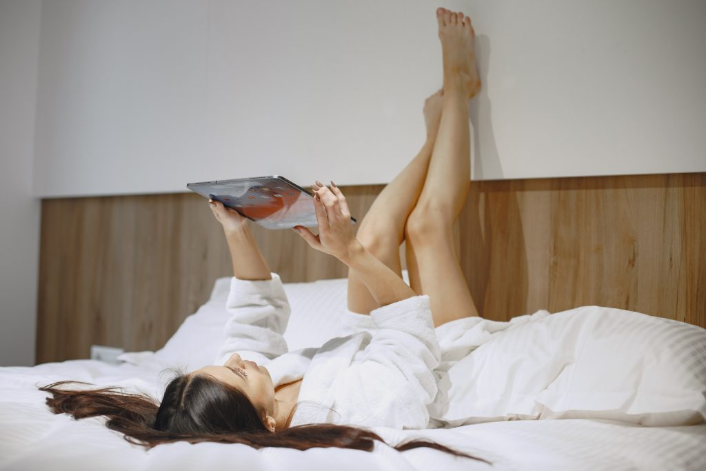 Woman in bed writing her dating diary